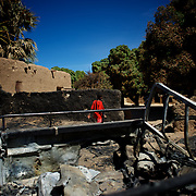 January 21, 2013 - Diabaly, Mali: A local passes by destroyed islamic militants' armoured vehicles in central Diabaly, a day after Mali government troops regain control of the city. Diabaly was under islamist militants control since the 14th of January...Several insurgent groups have been fighting a campaign against the Malian government for independence or greater autonomy for northern Mali, an area known as Azawad. The National Movement for the Liberation of Azawad (MNLA), an organisation fighting to make Azawad an independent homeland for the Tuareg people, had taken control of the region by April 2012...The Malian government pledge to the French army to help the national troops to stop the rebellion advance towards the capital Bamako. The french troops started aerial attacks on rebel positions in the centre of the country and deployed several hundred special forces men to counter attack the advance on the ground. (Paulo Nunes dos Santos/Polaris)
