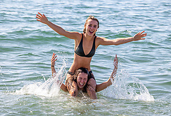 Licensed to London News Pictures. 07/09/2021. Brighton, UK. Students (blonde) Rebecca Martin 22 and Sophie Daily 20 cool off with a splash in the sea at Brighton Beach, East Sussex as weather forecaster predict a scorching 30c high today with September temperatures expecting to hit over 29c tomorrow. Photo credit: Alex Lentati/LNP