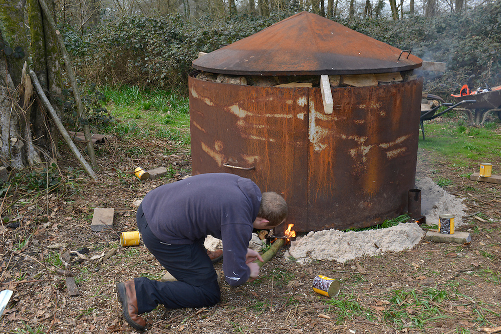 A charcoal kiln being lit in a deciduous woodland in southern England