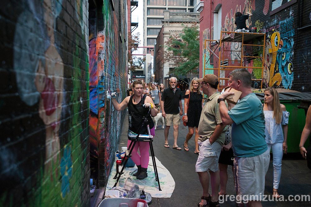 """Candace """"Sprite"""" Rood works on her mural late in the evening of August 10, 2017. Rood was participating in Freak Alley Gallery's seventh annual mural event in downtown Boise, Idaho.<br /> <br /> This is her fourth time she has participated in Freak Alley's mural event. This year she is adding on to the figure she started three years ago. The figures are coming out of the door like a pandora's box. She's been reading the Tibetan Book of the Dead and her mural is referring to the seven gods and their more visceral angry side. They do have a happier side which she would like to incorporate into the mural next year.<br /> <br /> Freak Alley Gallery's week long event provided an """"art-in-motion"""" experience as it welcomed the public to watch artists work on their murals."""