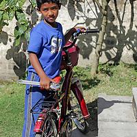 Asia, Nepal, Kathmandu. A Nepali boy and his bicycle.
