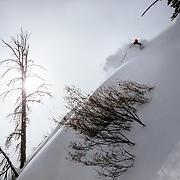 Tyler Hatcher skis the Teton Backcountry during a severe winter storm with a momentary sun break near Jackson Hole Mountain Resort, Teton Village, Wyoming.