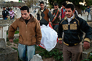 Men carry a set of remains to a grave in a Gaza City cemetery during a mass funeral 29 members of the Samouni family who died during Operation Cast Lead.