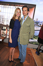ALEX GILKES and his wife MISHA NONOO-GILKES at Inception Group's Hamptons Garden Party to celebrate their collaboration with Embassy Gardens 2016 held at the Ballymore Marketing Suite, Nine Elms Lane, London on 12th July 2012.