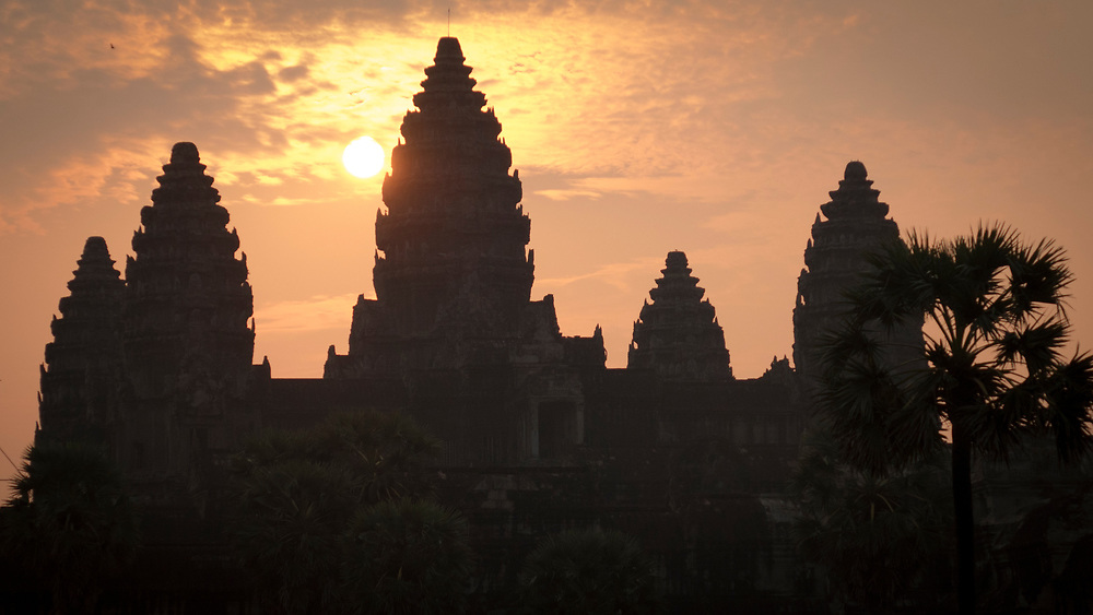 """Sunrise at Angkor Wat Temple, Siem Reap, Cambodia. Five towers of Angkor Wat symbolize the five mountains in India. The tallest tower represents Mount Meru, which is considered the home of the gods. <br /> The temple was originally dedicated to Lord Vishnu. The modern name, Angkor Wat, means """"City of Temples"""" in Khmer"""
