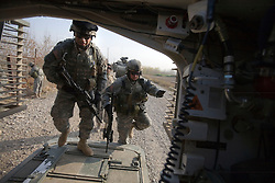 Maj. Jonathan Fox, right, enters the Stryker armored vehicle with other members of the 1st Infantry, 17th Regiment, as they help Iraqi forces patrol western Mosul, Iraq, Dec. 15, 2005. This is part of an effort to provide security in preparation for Iraq's first post-Saddam parliamentary elections. The western sector is home to Mosul's primarily Sunni population, which has been resistant to the American presence in Iraq.