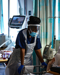 © Licensed to London News Pictures . 12/02/2021 .  Manchester , UK . A clinician stands and listens at the bedside of a patient on Ward 4 , the Respiratory Cohort Area . Inside Manchester Royal Infirmary , where patients are being treated for the effects of Coronavirus . Photo credit : Joel Goodman/LNP