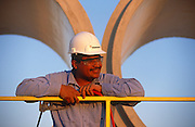 """A Mexican-born employee of Hanson Pipe & Products, at Grand Prairie, Texas, USA...They are inspcting the inner-surfaces and tongue and groove seals of the horizontal pipes wearing obligatory hard hats and corporate blue shirts. Precast concrete is made from a reusable mold or """"form"""" and cured in a controlled environment, then transported to the construction site and lifted into place. Used in the construction of commercial building components, bridges, manholes and retaining walls, these products are the strongest pipe available, designed and plant tested to resist any load required with a design life of 70-100 years. ..."""