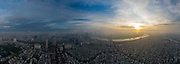 Aerial panorama of colorful sunrise and morning fog in Ho Chi Minh City featuring the Saigon River and landmark high rise buildings obscured by low cloud