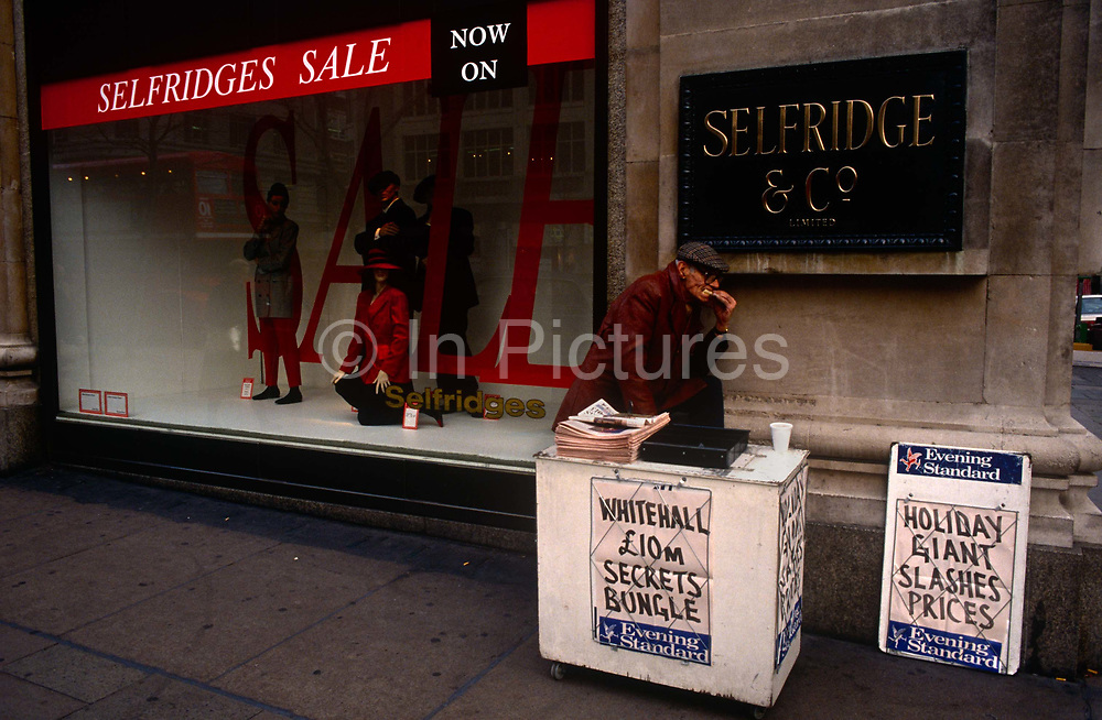 A newspaper seller rests for a moment to eat a sandwich. With a foot resting on his stall, he bites his snack while outside the large Selfridges department store on Oxford Street in central London. The headline refers to yet another governmental mistake involving vast amounts of public money on this day in 1992.