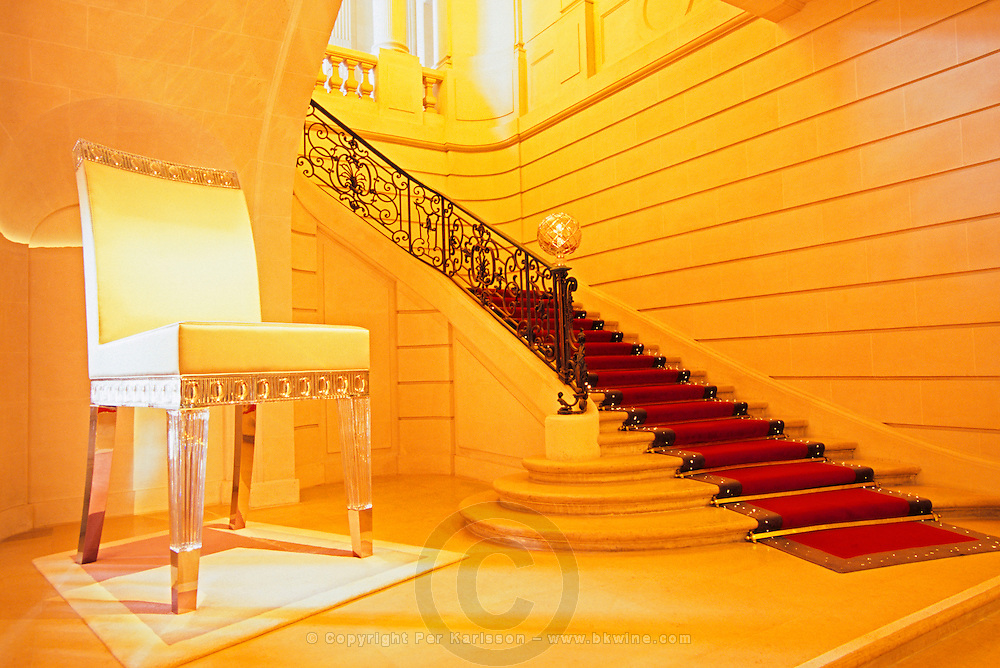 The main entrance with the gigantic satin and crystal chair by Philippe Starck and the red carpet with built in fibre optic lighting. At The Baccarat museum, shop, restaurant at the Hotel de Noailles in Paris. Designed by Philippe Starck. The Baccarat museum: the main stairway with the gigantic crystal chair designed by Philippe Starck and the red carpet with built-in crystal lights