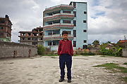 A young Nepalese boy stands outside a GoodWeave care home for young people who have been rescued from illegal labour in carpet factories. He had been working in an unlicensed carpet factory in Bhaktapur for two years before a GoodWeave Foundation inspector found him.  The conditions he was subjected to were very poor; he worked from 3am to 8pm, with only 1 hour for lunch and was beaten by his contractor. Because of the time spent on the Loom his fingers did not develop properly and he hasn't had an education. He is happy now to be living in the GoodWeave centre but wants to go back to his village to live with his parents, who are farmers, and to continue his education. Kathmandu, Nepal.