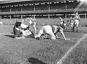 Kerry players O'Connell and McAuliffe rise slowly to their feet following a collision with Galway full back J Meade during the All Ireland Senior Gaelic Football Championship Final, Kerry vs Galway in Croke Park on the 27th September 1959. Kerry 3-7 Galway 1-4. Alied Irish Bank Ansley Bridge Poplar Rd, Fairview North Srand, East Wall Rd Houses, Shiriff St Church Clouds Howth Cornmarket, St Brendans March 1987