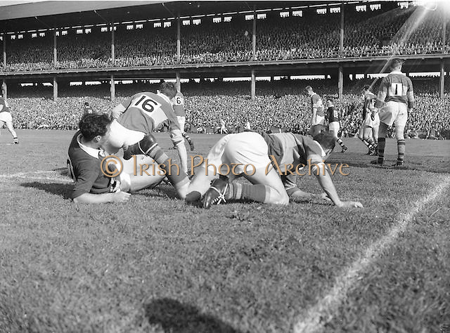 Kerry players O'Connell and McAuliffe rise slowly to their feet following a collision with Galway full back J Meade during the All Ireland Senior Gaelic Football Championship Final, Kerry vs Galway in Croke Park on the 27th September 1959. Kerry 3-7 Galway 1-4.