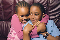 Young girl sitting on sofa hugging older brother,