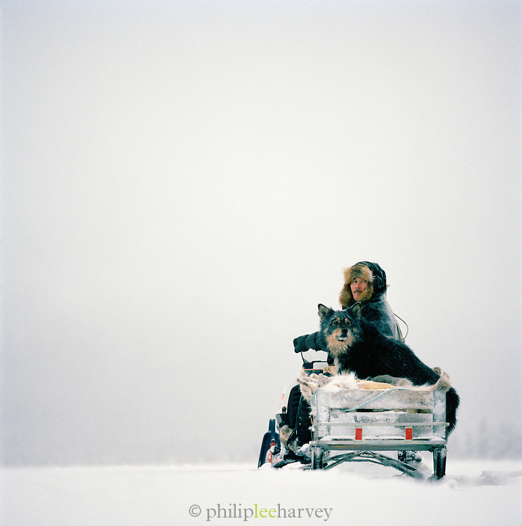 A Sami man with his dog on a sleigh in Lapland, Sweden