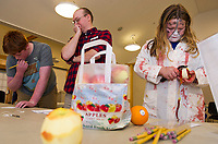 Andrew Decker tries to guess the order of the top 4 favorite Halloween candies (from Reese's, Skittles, M&M's and Snickers) with Youth Librarian John Locke while Delaney Sleeper peels an apple skin to predict her future love's initial during the Tween/Teen Halloween party at the Meredith Community Center on Tuesday afternoon.  (Karen Bobotas/for the Laconia Daily Sun)