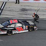 A pit crew member avoids the spun car of Jeremy Clements (51) during the Alert Today Florida 300 XFinity Series race at Daytona International Speedway on Saturday, February 21, 2015 in Daytona Beach, Florida.  (AP Photo/Alex Menendez)