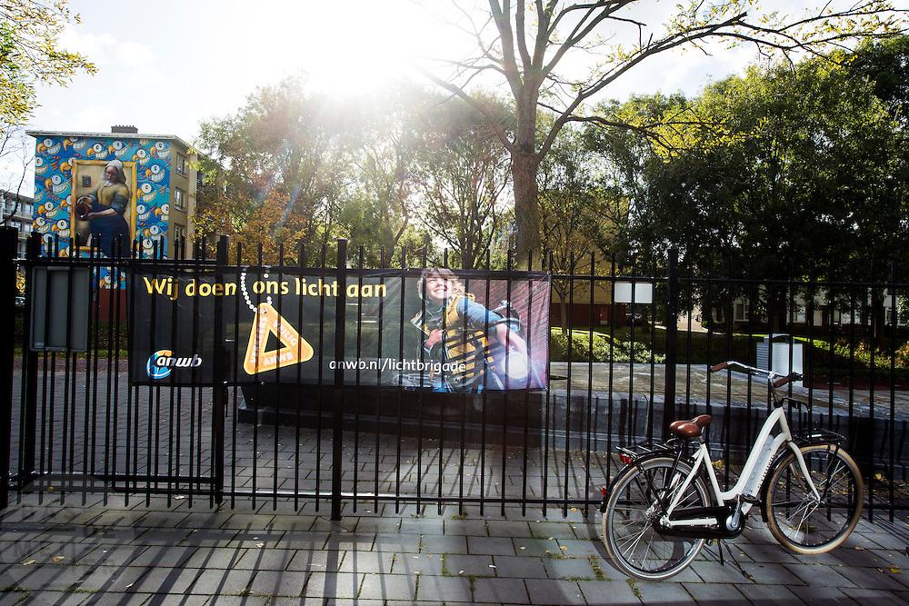 In Amsterdam hangt een spandoek van de ANWB campagne 'Wij doen ons licht aan' bij een schoolplein om scholieren aan te sporen fietsverlichting te gebruiken als het donker is.