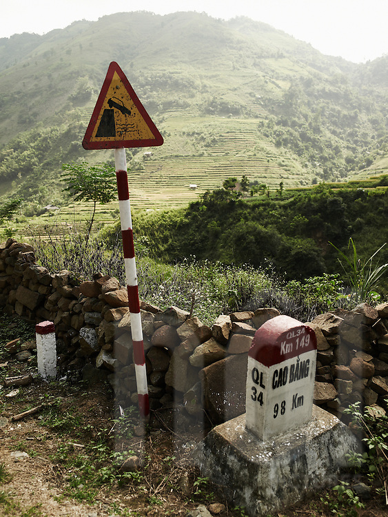 Kilometer marker indicates city of Cao Bang at 98 km. Old rusty safety road sign warns about fall risks due to the precipitous relief. Mountainous landscape in background.  Ha Giang province, Vietnam, Asia