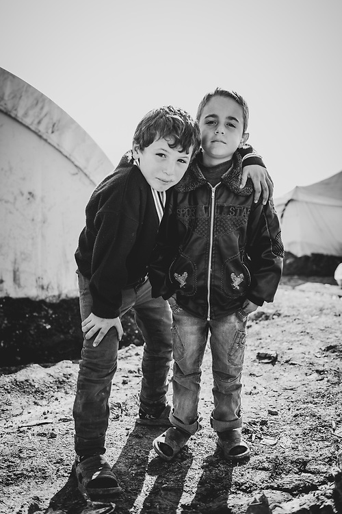 Atmeh, Syria - January 14, 2013: Two Syrian boys stand outside tents at the camp for internally displaced persons in Atmeh, located in northern Syria adjacent to the Turkish border.