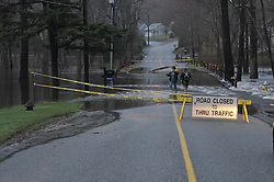 "Road Closed. Falls River Floods Across Dennison Road in Essex CT on 30 March 2010. People and ""Road Closed to Thru Traffic"" sign on sawhorse. Safety tape to warn people of going in the water, but these two folks seem not to care of the danger."