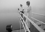 Lexie Palmore pilots the Delta Queen steamboat down the Ohio River, June, 1977.  She was the first female to become a riverboat pilot trainee, completing courses at the National River Academy in Helena, Arkansas.  She began her interest in riverboating as a passenger on the Delta Queen, later becoming a cabin maid.  She now pursues her life-long interest in painting from her home in Leadville, Colorado.<br /> <br /> Lexie and Captain Gabe Chengery