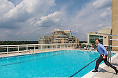 An executive jumps into a rooftop pool fully clothed