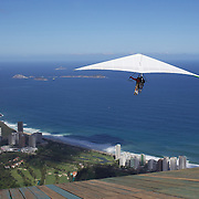 A tandem hang glider takes off above the hillside of Pedro Bonita high in the hills of Rio de Janeiro. Pilots of hang gliders and para gliders take tourists for tandem flights with breathtaking views of the city before landing on Sao Conrado beach. Rio de Janeiro,  Brazil. 9th September 2010. Photo Tim Clayton