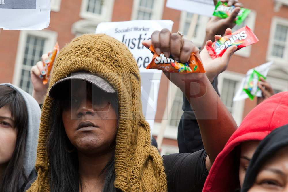 © Licensed to London News Pictures. 31/03/2012. London, England. Londoners holding empty bags of Skittles sweets protest outside the U.S. Embassy in Grosvenor Square, London on March 31, 2012 against the shooting of black youth Trayvon Martin by George Zimmermann in Sanford, Florida. Trayvon Martin was carrying an empty pack of Skittles when he died. Photo credit: Bettina Strenske/LNP