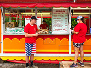 "26 JUNE 2020 - DES MOINES, IOWA:HUNTER (first name only) and BRENDA SMITH PARISH wait for customers at a booth selling fried potatoes and pork loin sandwiches at Fair Food Friday in Des Moines. The 2020 Iowa State Fair, like many state fairs in the Midwest, has been cancelled this year because of the COVID-19 (Coronavirus) pandemic. The cancellation of the fair left many small vendors stranded with no income. Some of the fair food vendors in Iowa started ""Fair Food Fridays"" on a property a few miles south of the State Fairgrounds. People drive up and don't leave their cars while vendors bring them the usual midway fare; corndogs, fried tenderloin sandwiches, turkey legs, deep fried Oreos, lemonaide and smoothies. Fair Food Friday has been very successful. The vendors serve 450-500 people per Friday and during the lunch rush people wait in line in their cars 30 - 45 minutes to place an order.     PHOTO BY JACK KURTZ"