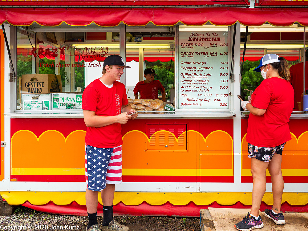 """26 JUNE 2020 - DES MOINES, IOWA:HUNTER (first name only) and BRENDA SMITH PARISH wait for customers at a booth selling fried potatoes and pork loin sandwiches at Fair Food Friday in Des Moines. The 2020 Iowa State Fair, like many state fairs in the Midwest, has been cancelled this year because of the COVID-19 (Coronavirus) pandemic. The cancellation of the fair left many small vendors stranded with no income. Some of the fair food vendors in Iowa started """"Fair Food Fridays"""" on a property a few miles south of the State Fairgrounds. People drive up and don't leave their cars while vendors bring them the usual midway fare; corndogs, fried tenderloin sandwiches, turkey legs, deep fried Oreos, lemonaide and smoothies. Fair Food Friday has been very successful. The vendors serve 450-500 people per Friday and during the lunch rush people wait in line in their cars 30 - 45 minutes to place an order.     PHOTO BY JACK KURTZ"""