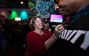 """Sayta Rhodes-Conway celebrates her victory over incumbent Paul Soglin by signing the """"Satya"""" sticker of security guard Jeff Thompson during the Madison Mayoral Election watch party at Prism Dance Club in Madison, WI on April 2, 2019."""