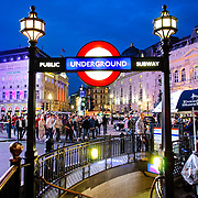 Entrance to the London Underground at Piccadilly Circus, at night, with a stairway leading down to the station. Editorial use only.