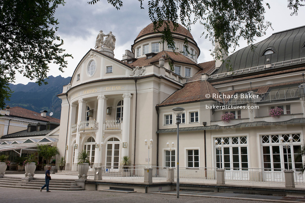 The Kurhaus in Meran-Merano on the Passer Promenade, South Tyrol, northern Italy - used for congresses, spa facilities and culture. Constructed at a time when Meran became a popular spa resort due to the frequent visits of Empress Elisabeth of Austria and the aristocracy. The building's original structure, which is today's west wing, was constructed in 1874 while the newer wing was added in 1912 and 1914 by the Viennese Jugendstil architect Friedrich Ohmann. The exterior features a large portico with columns and is decorated with allegorical statues.