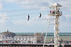 © Licensed to London News Pictures. 11/02/2018. Brighton, UK. Members of the public take a ride on the Zipwire attraction on the Brighton and Hove beach as sunshine and milder weather is hitting the seaside resort. Photo credit: Hugo Michiels/LNP