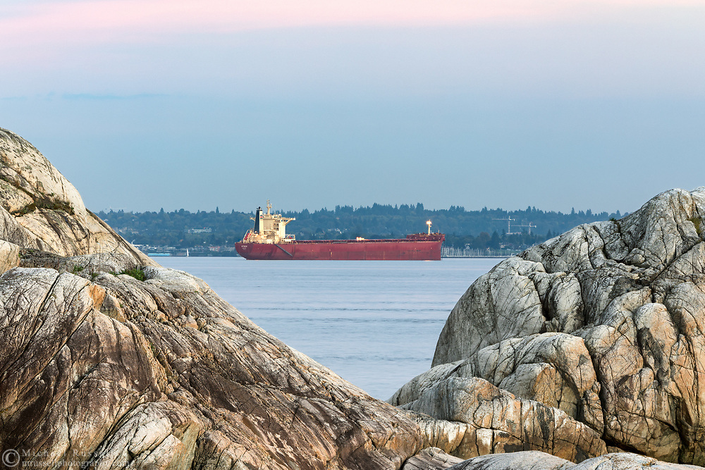 The Bulk Carrier Attikos anchored on English Bay during an early autumn evening in Vancouver, British Columbia, Canada.  Photographed from Point Atkinson in Lighthouse Park in West Vancouver with Point Grey (Vancouver) in the background.