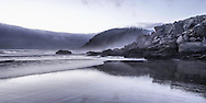 This photo was taken on the Oregon coast at low tide. You can see the tide line as indicated by the darker rocks which are covered in kelp. The dark area above the water on the left-hand side is a fog bank that began to recede at sunset, allowing for a bright sky at dusk.