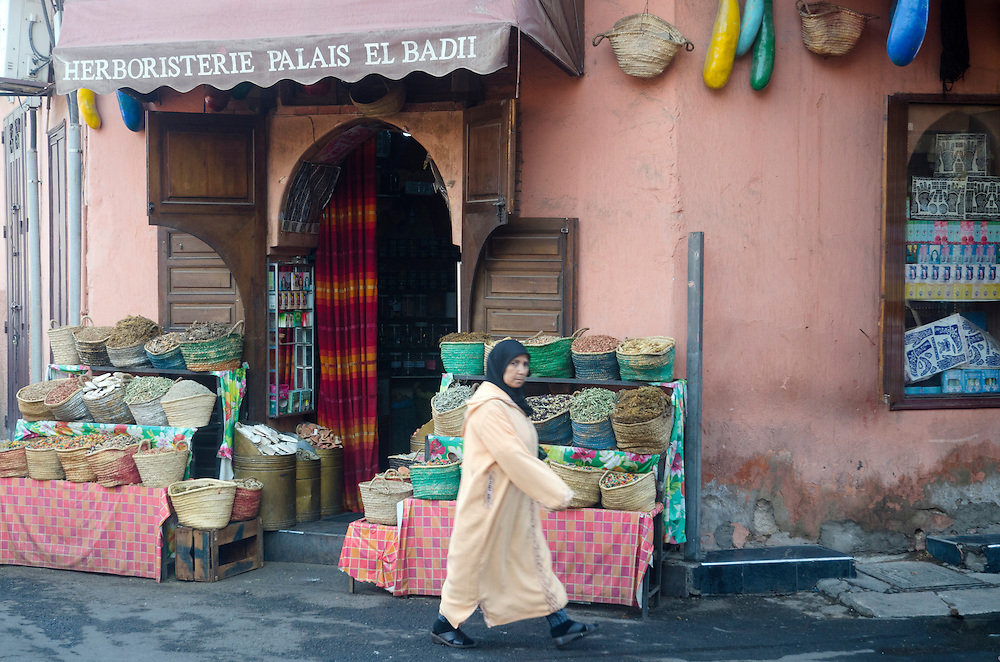 Woman walks past a herb and spice shop in Marrakech Morocco