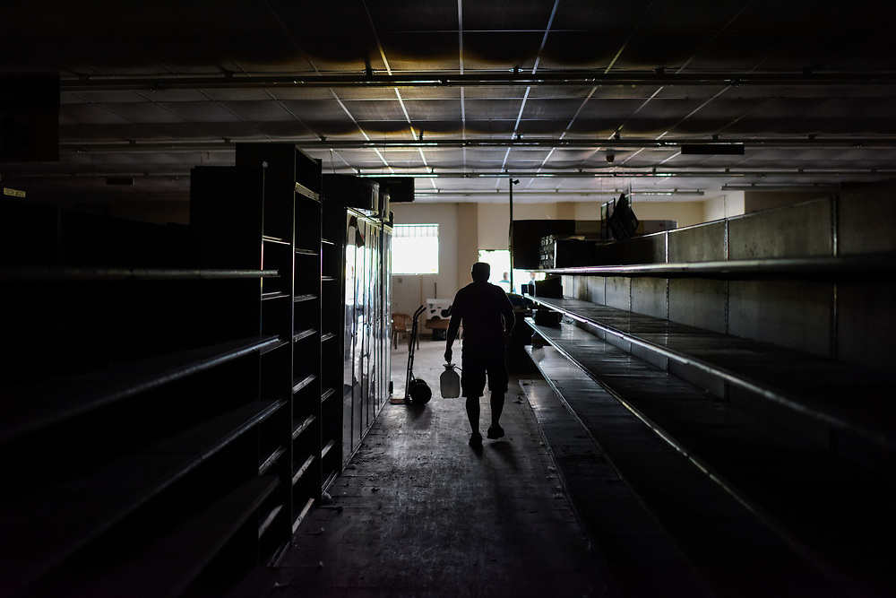 Jim Snoddy, co-owner of Snoddy's Store, walks along the unlit store aisles. Once full shelves now stand empty with tags helpfully pointing out nonexistent products. The lights remain off and the glass doors that once stood at the entrance of the store were removed, leaving only metal security bars that more resemble an entrance to a prison cell. The current Snoddy's building was completed in 1993, the same year of the flood that inundated the original Snoddy's located a short distance away. The new building featured flood walls built into the store itself as a means of protecting it from future floods; however, the water that inundated Snoddy's three months ago came not from outside but through the store's drains, rising over two feet before receding.