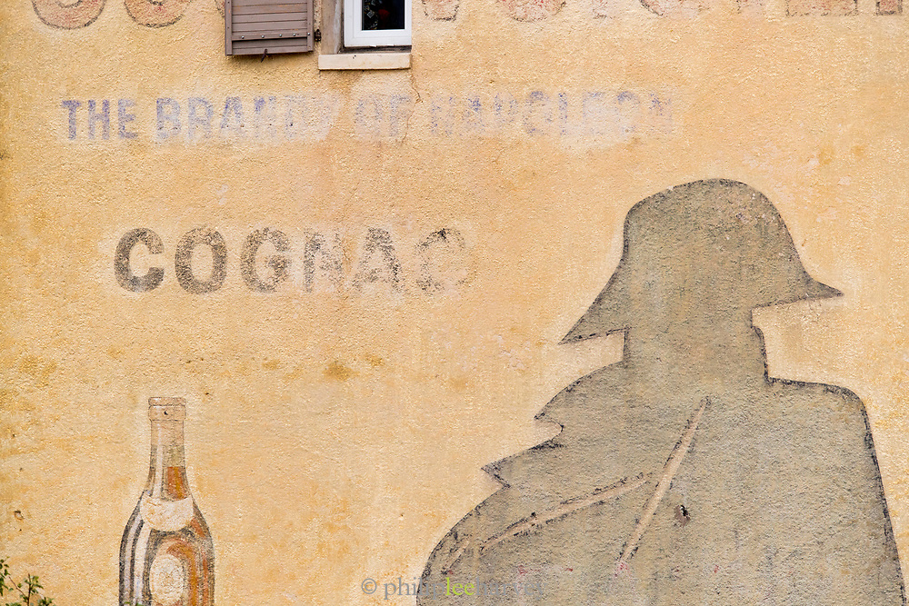 Painted on facade and faded advert for Courvoisier Cognac - Brandy of Napoleon, France.