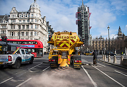 © Licensed to London News Pictures. 26/02/2018. London, UK. A glitter is seen spreading grit in front of the Houses of Parliament in central London, as a cold front sweeps in from the east. Up to 20cm of snow are expected in parts of the UK, with temperatures feeling as low as -15C in some places. Photo credit: Ben Cawthra/LNP