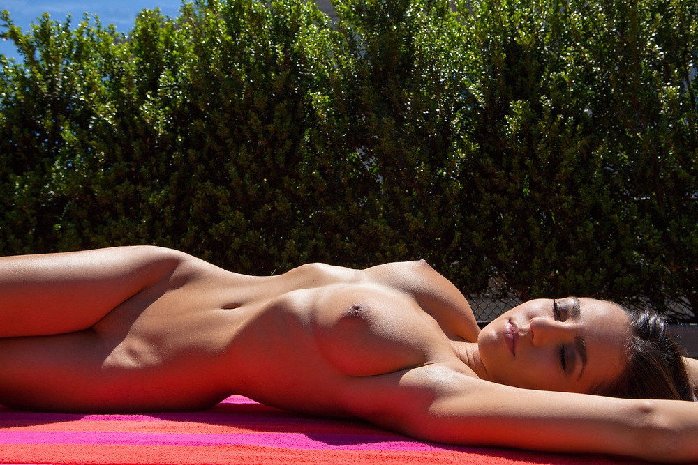Torso of woman reclining on a red striped beach towel sunbathing in the nude