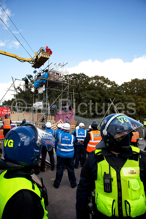 Protesters who barricaded themselves above the entrance to the Dale Farm travellers' site have been removed by police as bailiffs prepare to move in. Essex Police cleared the scaffolding structure so it could be dismantled and machinery driven in by bailiffs to evict the travellers. On Wednesday night Essex Police said that over the course of the day 23 people had been arrested. Clearance of Dale Farm prior to eviction. Riot police and bailiffs were present on 19th October 2011, as a scaffolding gantry was cleared of protesters so the site could be cleared. Dale Farm is part of a Romany Gypsy and Irish Traveller site on Oak Lane in Crays Hill, Essex, United Kingdom. Dale Farm housed over 1,000 people, the largest Traveller concentration in the UK. The whole of the site is owned by residents and is located within the Green Belt. It is in two parts: in one, residents constructed buildings with planning permission to do so; in the other, residents were refused planning permission due to the green belt policy, and built on the site anyway.