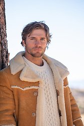 hot rugged man in a shearling coat outdoors