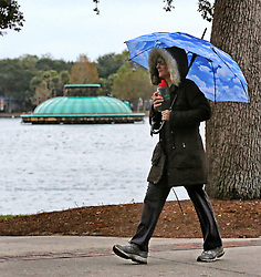 January 2, 2018 - Orlando, FL, USA - With frigid temperatures blanketing most of the country, a pedestrian in Lake Eola Park bundles up against the chill, in Orlando, Fla., on Tuesday, Jan. 2, 2018. Lows are forecast to dip below freezing in central Florida this week. (Credit Image: © Joe Burbank/TNS via ZUMA Wire)