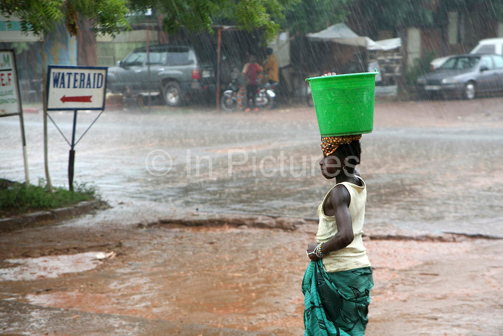 A young woman carries a bucket of water on her head during a downpour on the streets of Bamako during the rainy season. The downpours can be torrential in Mali at times.