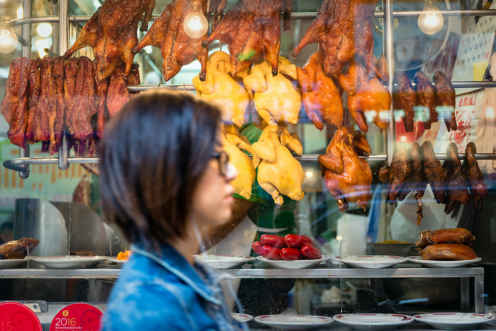 Blurred motion of woman passing window of barbeque restaurant in Central, Hong Kong