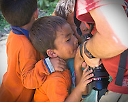 Children jostle to see their photos in the back of a camera, Punakha valley, Bhutan