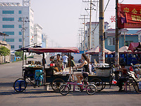 Young girl on bicycle riding past a street food vender in Wenzhou, China.